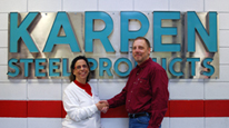 Rachel Smith & Eric Henken in front of the sign from the original Karpen Steel plant from Long Island, NY, which now hangs in the NC office.